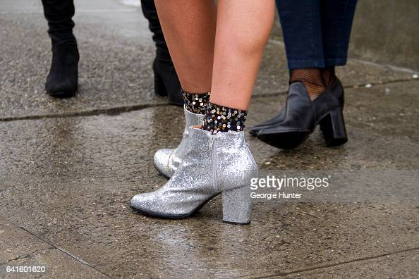 Guest is seen at Spring Studios outside the Lacoste show wearing silver glitter ankle boot with block heel and sequin stockings on February 11 2017...