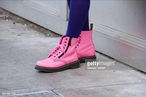 Guest is seen at Spring Studios outside the Lacoste show wearing pink Dr Martens lace up boots and purple stockings on February 11 2017 in New York...