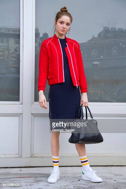 Guest is seen at Spring Studios outside the Lacoste show wearing red sports jacket with white detail blue ribbed knit tight three quarter length...