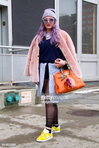 Guest is seen at Spring Studios outside the Lacoste show with purple dyed hair wearing light pink coat purple sunglasses with mirror frames blue over...