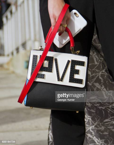 Guest is seen at Spring Studios outside the Phillip Lim show wearing black suit pants and black and white bag with 'love' lego detail red carry...