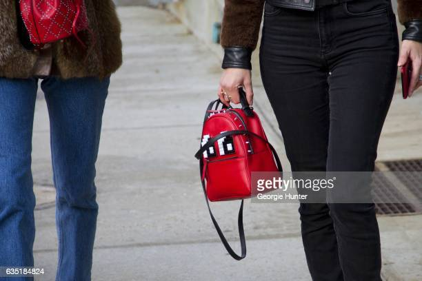 Guest is seen at Spring Studios outside the Phillip Lim show wearing black jeans and mini red leather backpack with lego eyes thin black shoulder...
