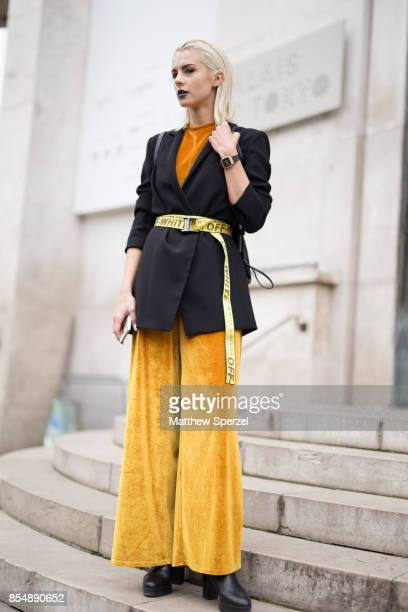 A guest is seen attending AALTO during Paris Fashion Week wearing a black blazer gold pants and OffWhite belt on September 27 2017 in Paris France