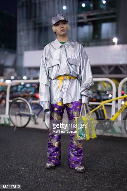 A guest is seen attending Fashion Hong Kong during Tokyo Fashion Week wearing a silver coat with yellow belt and purple silk ornate design pants on...