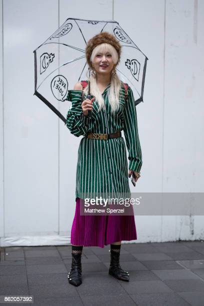A guest is seen attending PERMINUTE and tiit tokyo during Tokyo Fashion Week wearing a green stripe shirt with Moschino belt and purple skirt on...