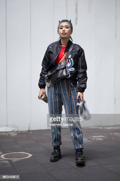 A guest is seen attending thibaut during Tokyo Fashion Week wearing a black leather jacket with red shirt and striped pants on October 17 2017 in...
