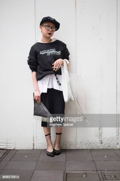 A guest is seen on the street wearing a black beret black and white sweatshirt white top black skirt and black shoes during Tokyo Fashion Week on...