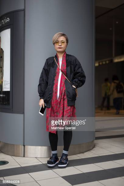 A guest is seen on the street wearing a black coat red dress and blue leather sandals during Tokyo Fashion Week on March 20 2017 in Tokyo Japan