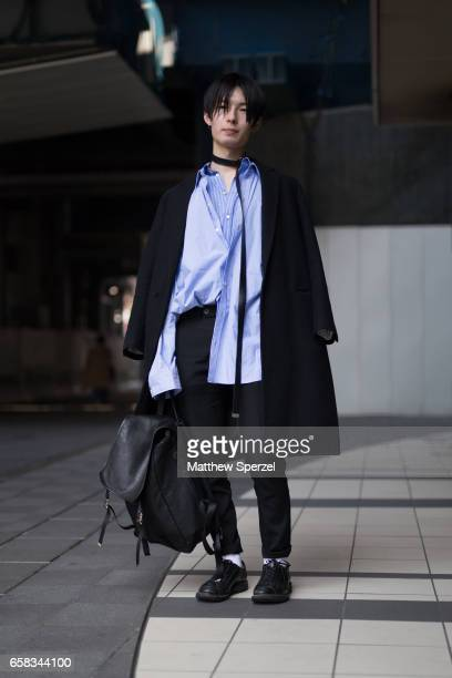 A guest is seen on the street wearing a black coat with blue oversized shirt and black belt collar with black bag during Tokyo Fashion Week on March...