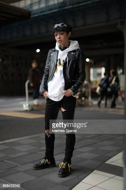 A guest is seen on the street wearing a black leather jacket white hoodie and torn black pants during Tokyo Fashion Week on March 23 2017 in Tokyo...