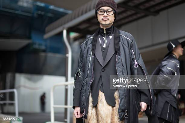 A guest is seen on the street wearing a black with gold zipper coat black blazer fur pants and brown hat during Tokyo Fashion Week on March 23 2017...