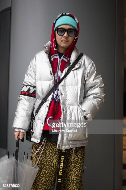 A guest is seen on the street wearing a blue beanie cap red peace sign hoodie silver down jacket and gold leopard print pants during Tokyo Fashion...