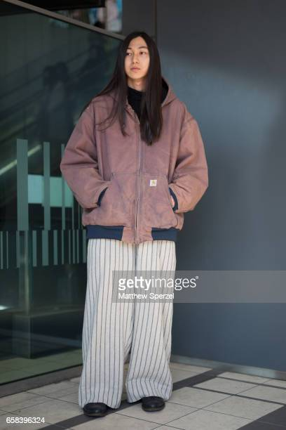 A guest is seen on the street wearing a Carhartt coat and navy/white pinstripe pants during Tokyo Fashion Week on March 22 2017 in Tokyo Japan