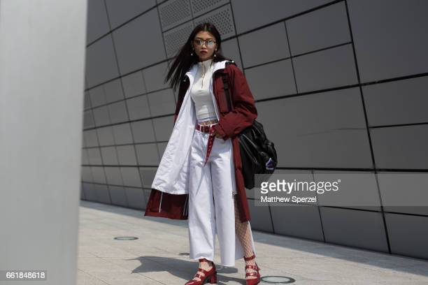 A guest is seen on the street wearing a crimson and white coat white top white pants crimson belt and shoes during HERA Seoul Fashion Week on March...