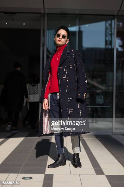 A guest is seen on the street wearing a gold and navy coat with red sweater and navy/cream pants during Tokyo Fashion Week on March 22 2017 in Tokyo...