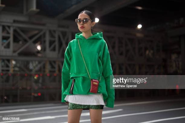 A guest is seen on the street wearing a green hoodie with red bag and green skirt during Tokyo Fashion Week on March 23 2017 in Tokyo Japan