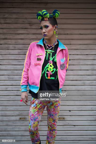 A guest is seen on the street wearing a pink and blue jacket neon green and black shirt multicolor leggings during Tokyo Fashion Week on March 22...