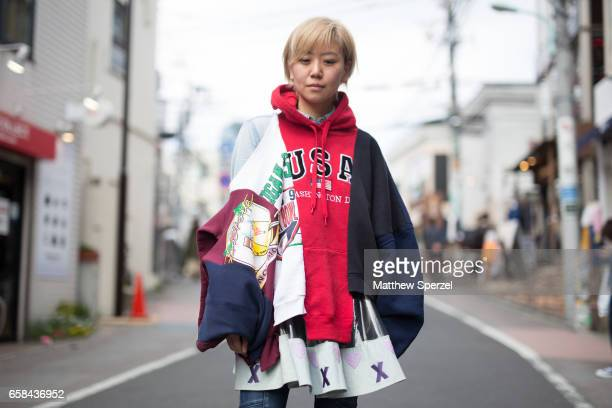 A guest is seen on the street wearing a pink USA hoodie white/maroon/navy jacket during Tokyo Fashion Week on March 24 2017 in Tokyo Japan