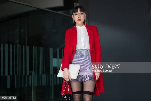 A guest is seen on the street wearing a red coat striped skirt and white shirt with white bag during Tokyo Fashion Week on March 24 2017 in Tokyo...