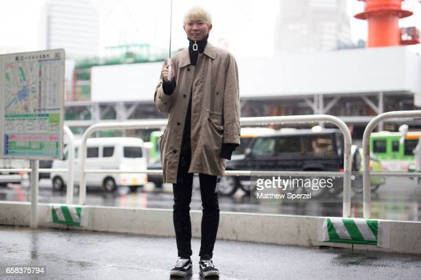 A guest is seen on the street wearing a taupe trench coat with black sweater and pants during Tokyo Fashion Week on March 21 2017 in Tokyo Japan