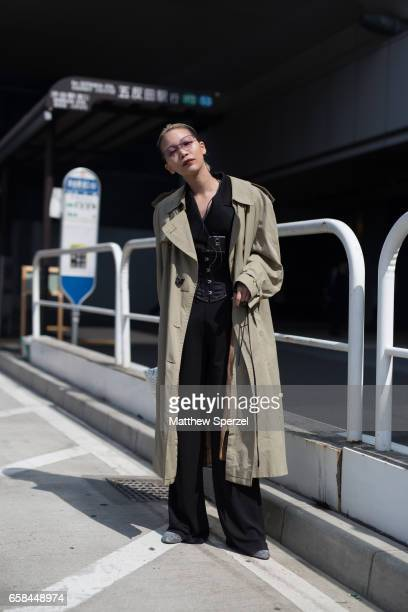 A guest is seen on the street wearing a taupe trench coat with black outfit and corset during Tokyo Fashion Week on March 25 2017 in Tokyo Japan