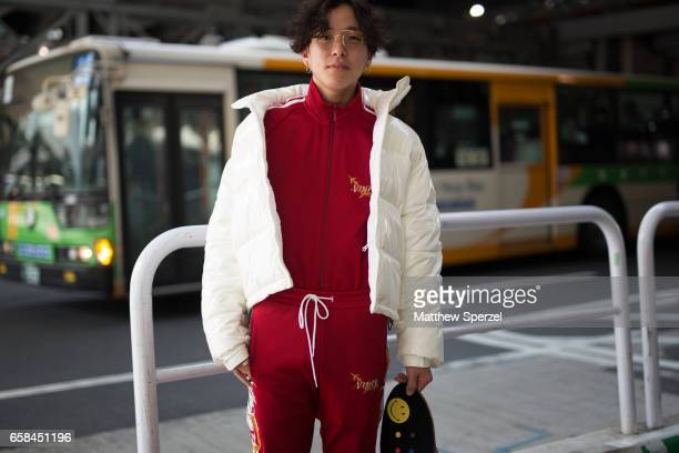 A guest is seen on the street wearing a white down jacket with red sweatsuit and Supreme skateboard bag during Tokyo Fashion Week on March 25 2017 in...