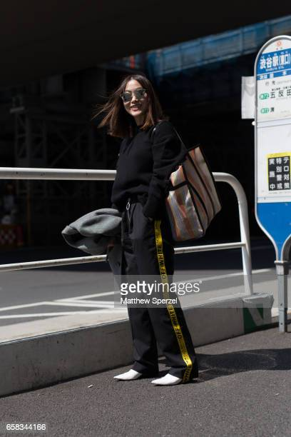 A guest is seen on the street wearing an all black outfit with yellow stripe pants during Tokyo Fashion Week on March 20 2017 in Tokyo Japan