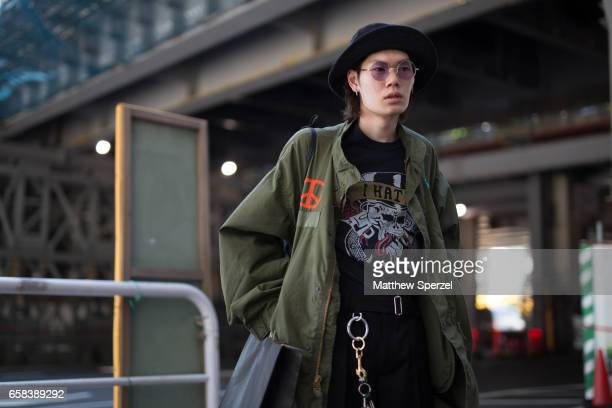 A guest is seen on the street wearing an army green long coat black brim hat black zipper detail pants and boots during Tokyo Fashion Week on March...