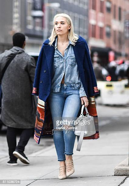 A guest is seen outside the DKNY show wearing a jean shirt ripped blue jeans and a blue and brown graphic coat during New York Fashion Week Women's...