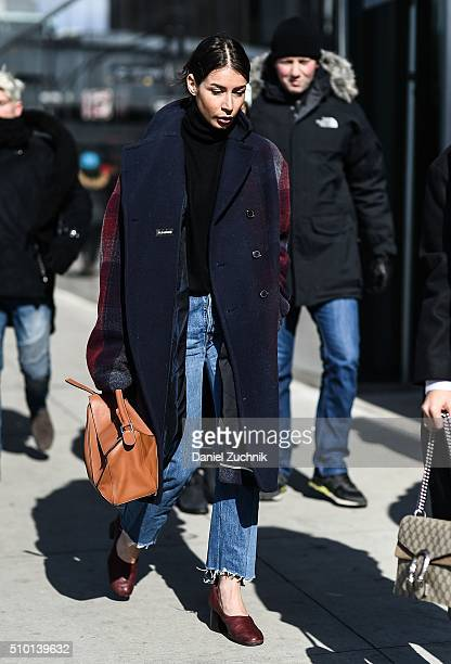A guest is seen outside the Tibi show wearing a blue and plaid coat with blue jeans brown shoes and a brown bag during New York Fashion Week Women's...