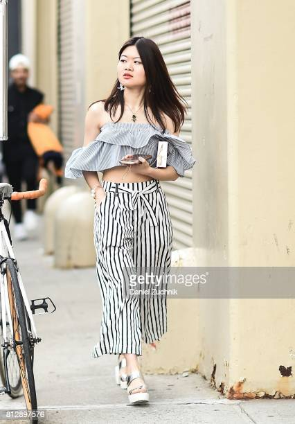 A guest is seen wearing a black and white striped crop top and pants outside the Carlos Campos show during New York Fashion Week Men's S/S 2018 at...