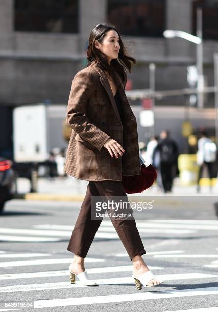 A guest is seen wearing a brown jacket and brown pants with red bag outside the Brock Collection during New York Fashion Week Women's S/S 2018 at...