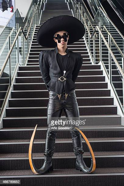 A guest is seen wearing vintage hat and jacket trousers by Yves Saint Laurent shoes by Garrison and spectacles by Jeremy Scott during the Mercedes...