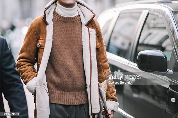 A guest is wearing a brown aviator jacket with white inner lining a white turtleneck tshirt and a brown wool pull over outside the Paul Smith show...