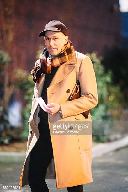 A guest is wearing a brown cap a brown scarf and camel coat outside the Thom Browne show during Paris Fashion Week Menswear Fall/Winter 2017/2018 on...