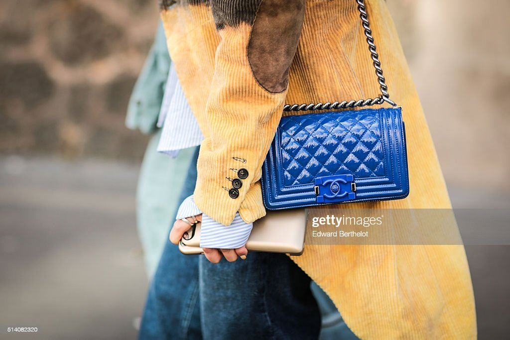 A guest is wearing a Chanel blue bag and a yellow coat before the John Galliano show during Paris Fashion Week Womenswear Fall Winter 2016/2017 on...