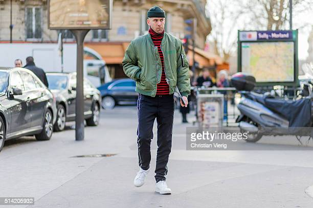 A guest is wearing a green bomber jacket jogger pants white sneaker and a striped turtleneck outside Hermes during the Paris Fashion Week Womenswear...