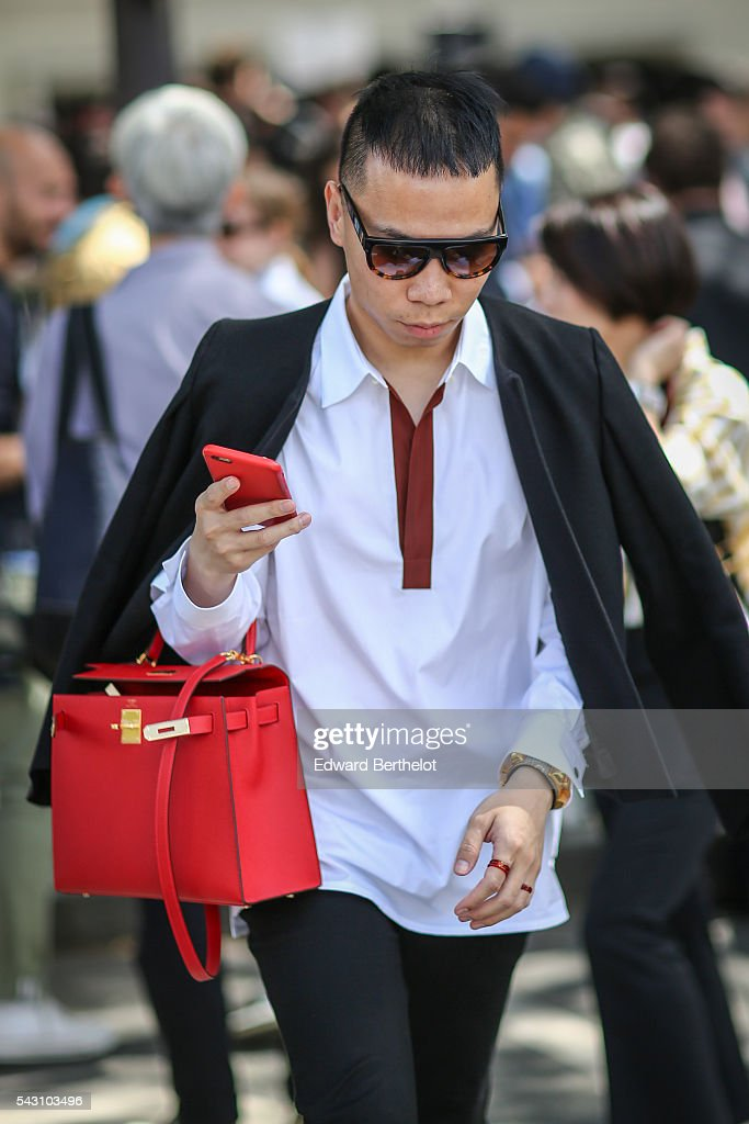 A guest is wearing a Hermes red bag, after the Dior show, during Paris Fashion Week Menswear Spring/summer 2017, on June 25, 2016 in Paris, France.