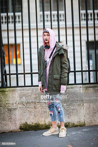 A guest is wearing a pink hoodie a green jacket blue denim ripped jeans and shoes outside the Balmain show during Paris Fashion Week Menswear...