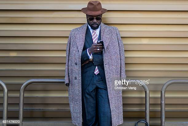 A guest is wearing a wool coat suit hat and sunglasses on January 10 2017 in Florence Italy