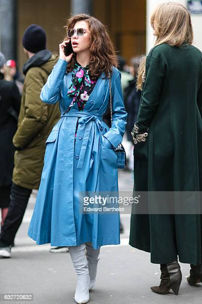 A guest is wearing sunglasses a blue crocodile leather bag a blue rain coat a floral print top and white boots outside the Elie Saab show during...