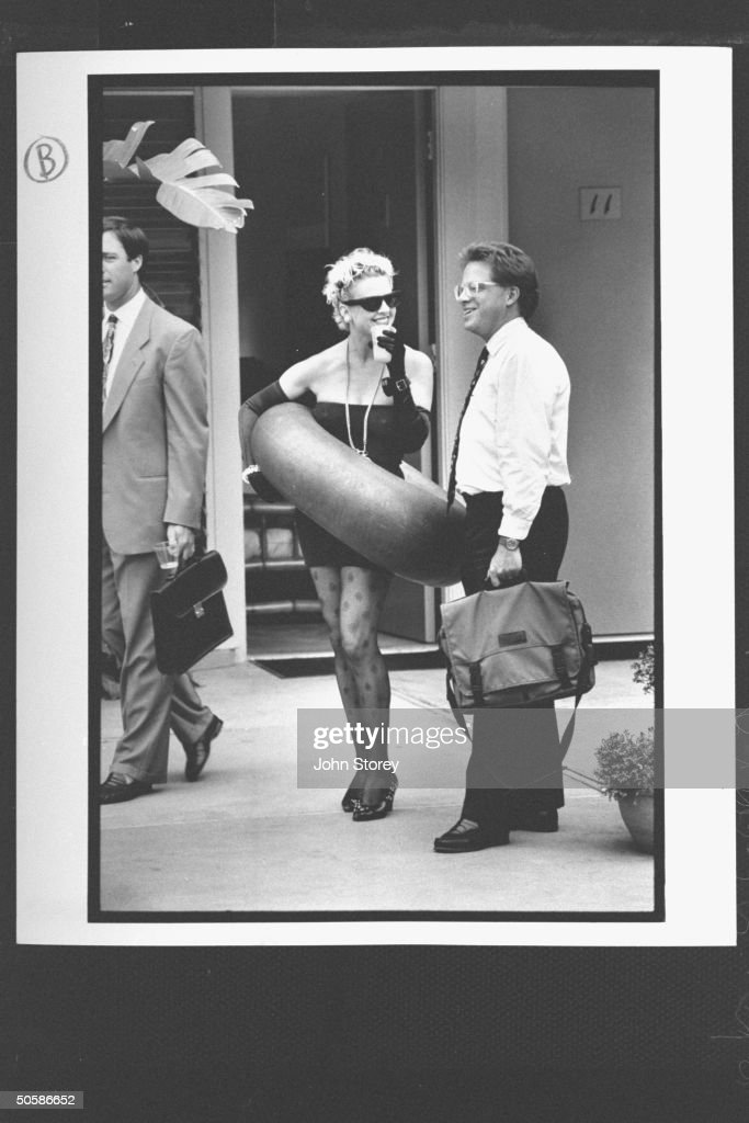Guest of Phoenix Inn, Lisa Streeter, wearing sunglasses & skimpy strapless minidress as she carries an inner tube around her waist while sipping drink & chatting w. a young businessman who is holding his canvas briefcase in poolside area.