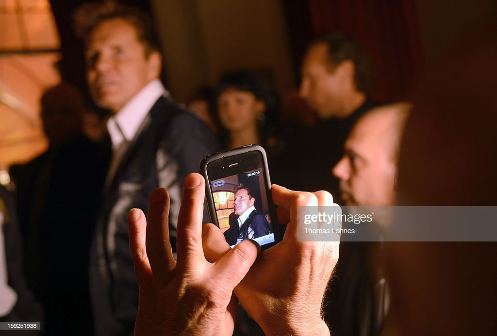 A guest photographs Entertainer and Singer Dieter Bohlen who presents his wallpaper collection 'Dieter Bohlen - it's different' during a party in the restaurant 'Druckwasserwerk' in Frankfurt/Main on January 10, 2013 in Frankfurt am Main, Germany. The self-proclaimed 'Poptitan' has launched its own wallpaper collection with the wallpaper manufacturer Pickhardt and Sieberthas from Gummersbach.
