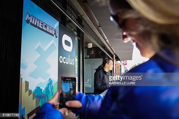 A guest photographs signs at the entrance of the Minecraft for Gear VR press demonstration and reception in San Francisco California on March 15 2016...