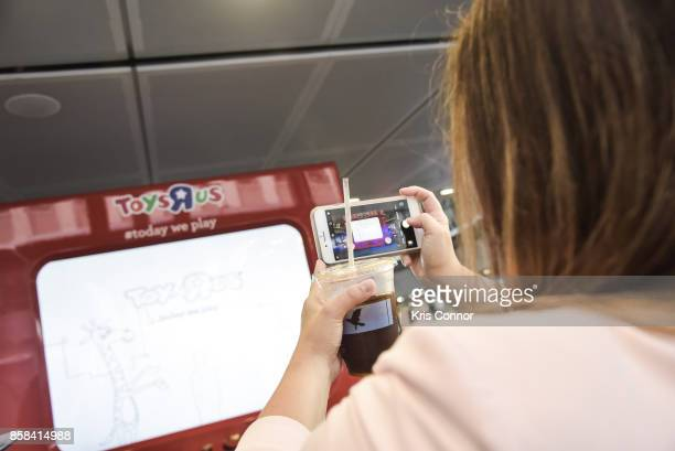 A guest plays with a giant Etch A Sketch during the 'Toys 'R' Us Takes Over Fulton Street Subway Station with Giant Etch A Sketch' event at Fulton...