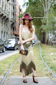 A guest poses in a vintage dress and a Louis Vuitton clutch on September 17 2014 in Milan Italy
