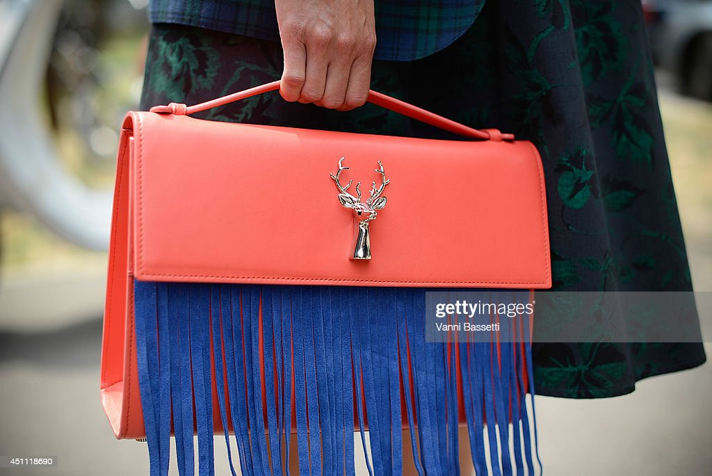 A guest poses in a vintage dress and Savas bag before Gucci show on June 23, 2014 in Milan, Italy.