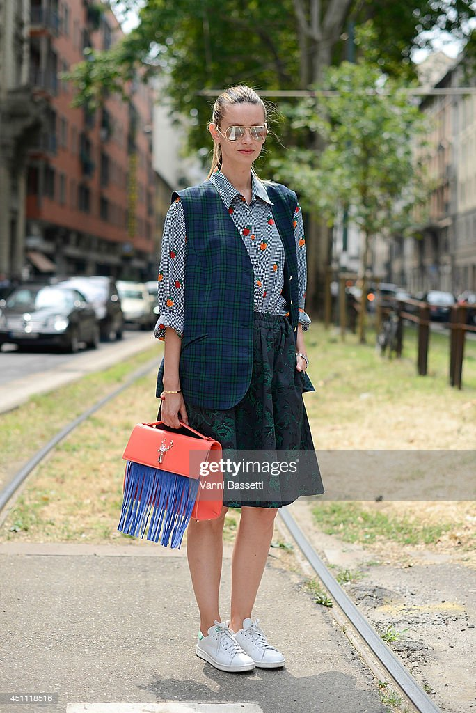 A guest poses in a vintage dress, Savas bag and Adidas shoes before Gucci show on June 23, 2014 in Milan, Italy.