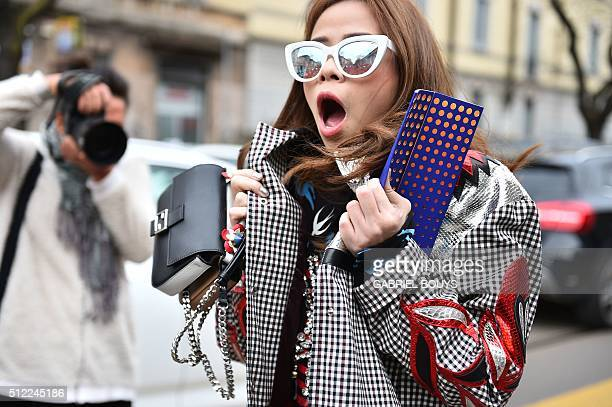 A guest poses in the street before the show for fashion house Fendi during the Autumn / Winter 2016 Milan Fashion Week on February 25 2016 AFP PHOTO...