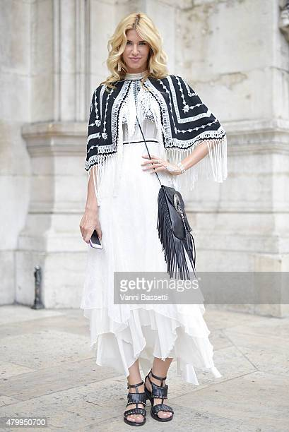 A guest poses wearing a Chanel dress and YSL bag before the Alexis Mabille presentation at the Opera Garnier on July 8 2015 in Paris France